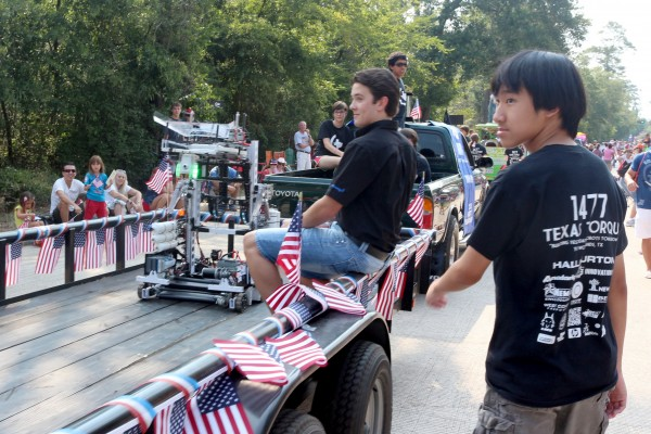 Texas Torque members Henning Skau (left) and Brian Wang (right) travel in the parade with Sonic in tow.