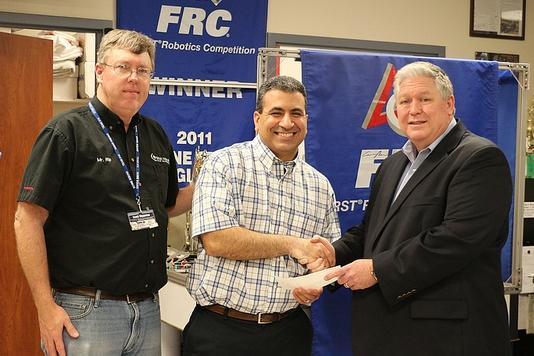 Matt Davies receives the $10,000 check from Alan Coats.
